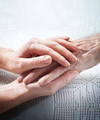 a pair of young hands compassionately comforting a frail elderly hand