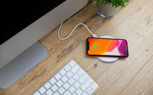 Wireless charger charging an iphone on a desk