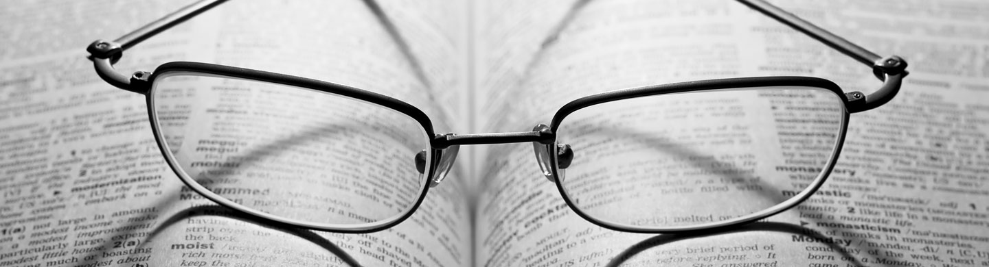 spectacles on top of a dictionary